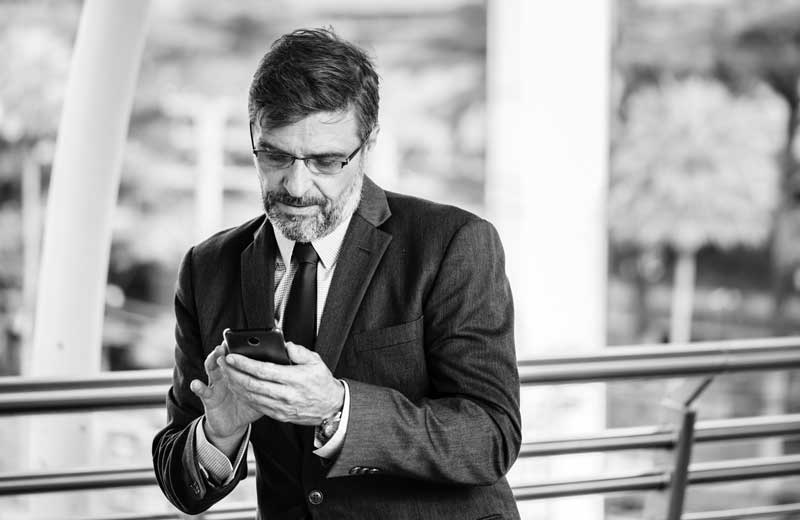 A business man near a fence using his smartphone